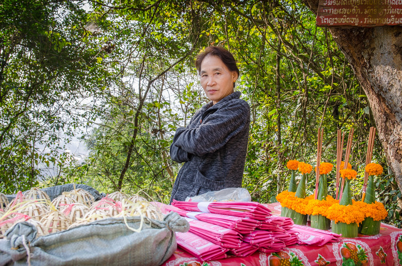 Woman selling offerings on Mount Phousi. The little cage/baskets contain live birds. Don't buy these!