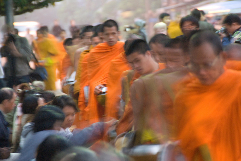 Blurred photo of monks collecting alms during ceremony at Luang Prabang, Laos