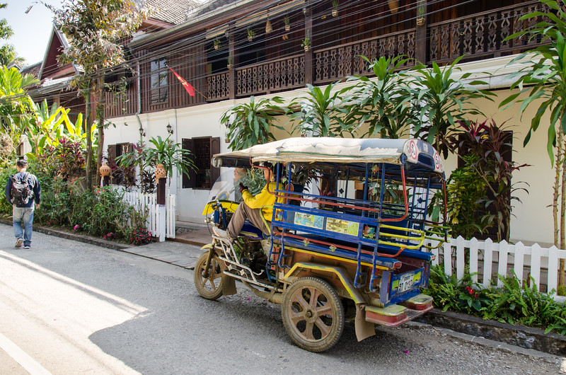 A tuk-tuk in front of and old colonial building...a hotel now.