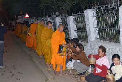 Tourists giving alms during ceremony in Luang Prabang, Laos