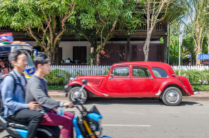 Antique Citroen in front of colonial building with scooter passing.