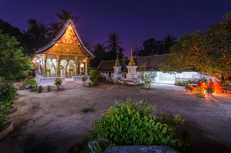 A small, beautiful temple at night. Monks keeping warm by the fire.