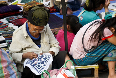 A woman at the night market hand-stitches a quilt in Luang Prabang, Laos