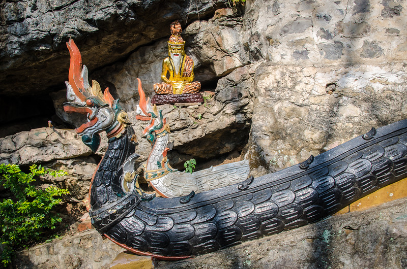 A small bearded buddha with tiger stripe pajamas behind two dragons.