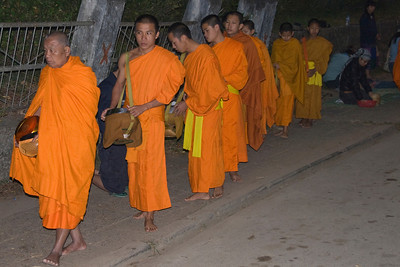 Barefoot monks collecting alms during ceremony in Luang Prabang, Laos