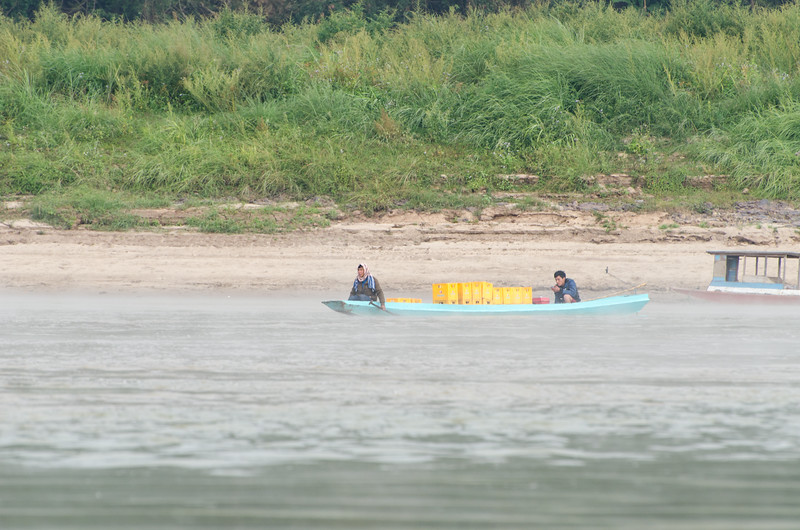 Men with a small load of cargo crossing the Mekong early on a misty morning.