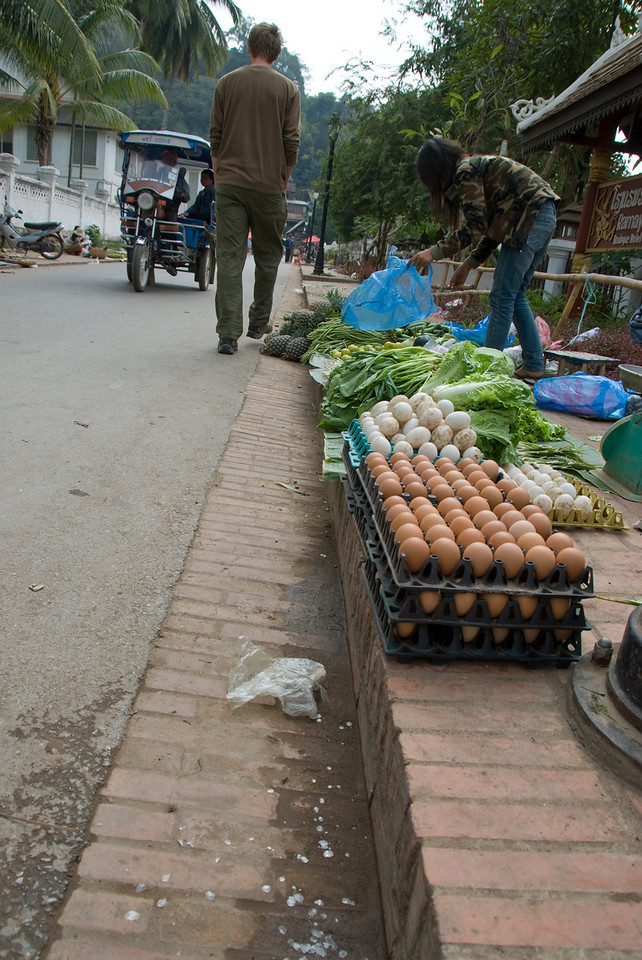 Vendor selling vegetables and eggs on sidewalk at Luang Prang, Laos