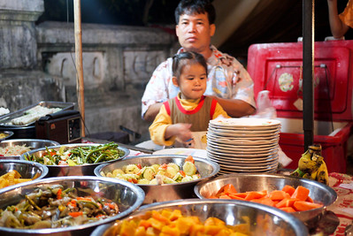 This little girl helps her dad dole out the buffet plates in Luang Prabang, Laos