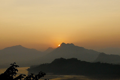The last pieces of light cast an orange glow on the Mekong River in Luang Prabang, Laos