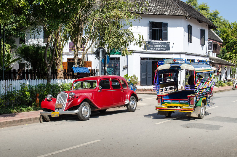 Antique Citroen in front of colonial building with tuk-tuk passing.