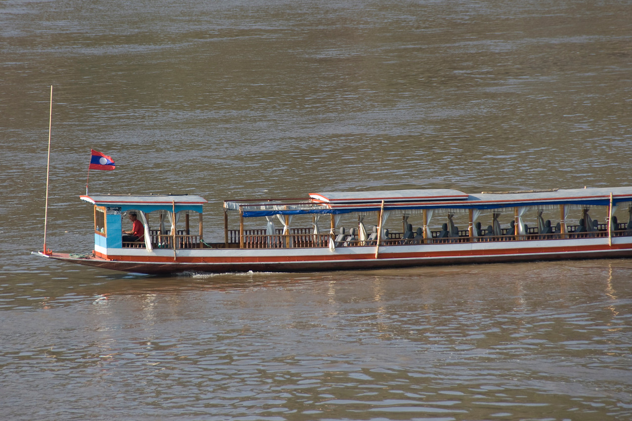 Empty boat cruising down Mekong River in Luang Prang, Laos