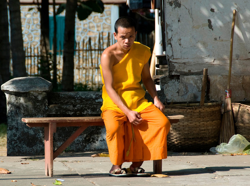 Monk sitting on a wooden bench in Luang Prang, Laos