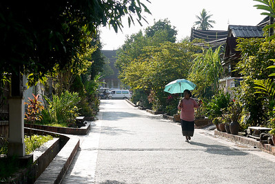 A woman takes a quiet early morning walk in Luang Prabang, Laos