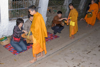 Locals kneeling on side walk during alms giving ceremony in Luang Prabang, Laos