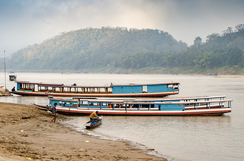 Lao slow boats on the bank of the Mekong in Luang Prabang on a misty, cool morning.
