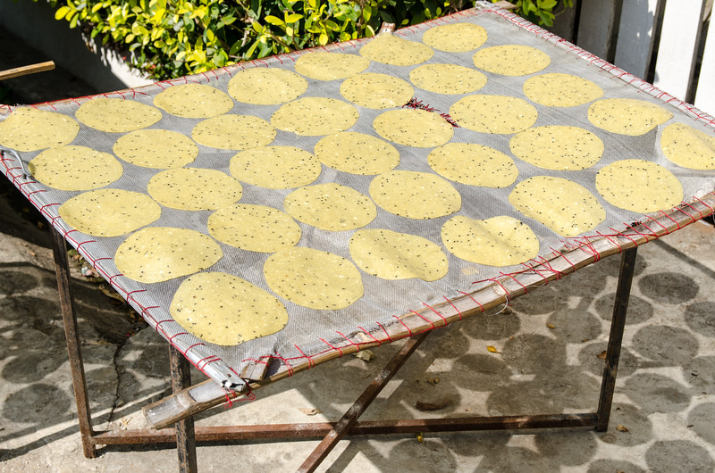 Flat cakes made of coconut and sesame drying on a rack.