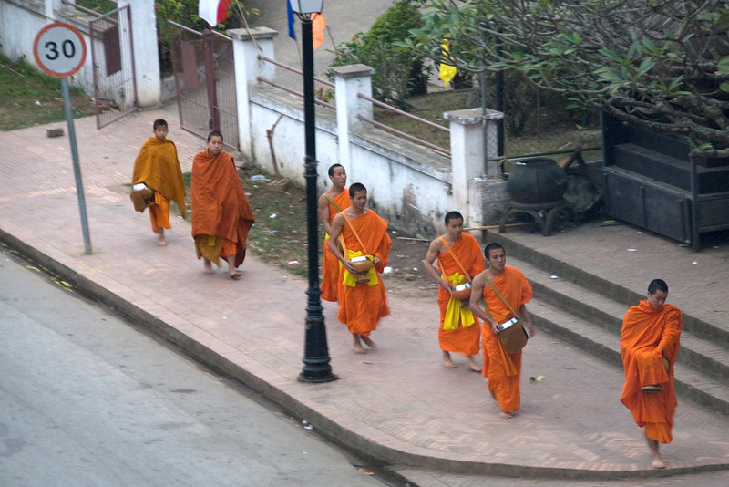 Monks walking on barefoot during alms-giving ceremony in Luang Prabang, Laos