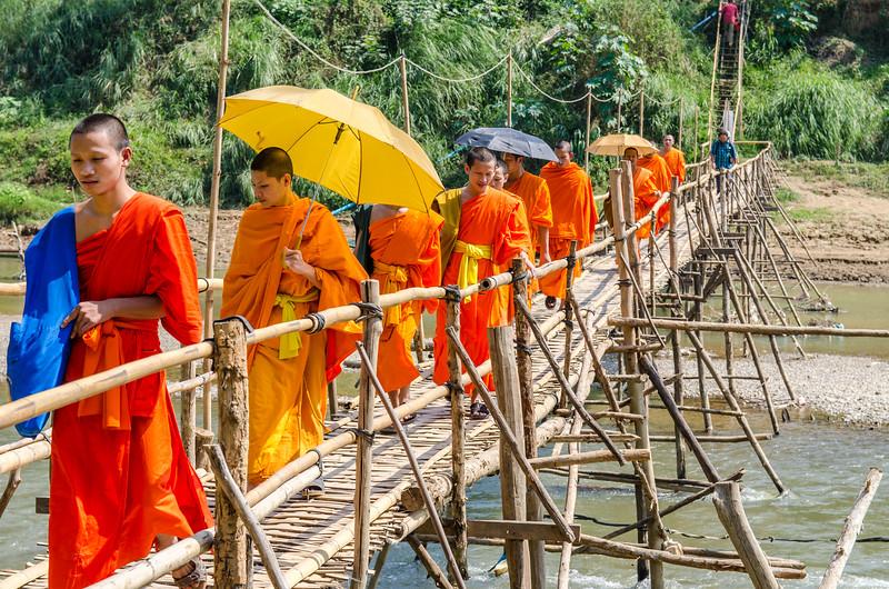 Buddhist monks crossing a bamboo bridge over the Nam Khan River, Luang Prabang.