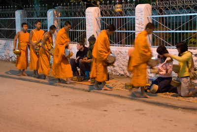 Tourists participating at alms giving ceremony in Luang Prang, Laos