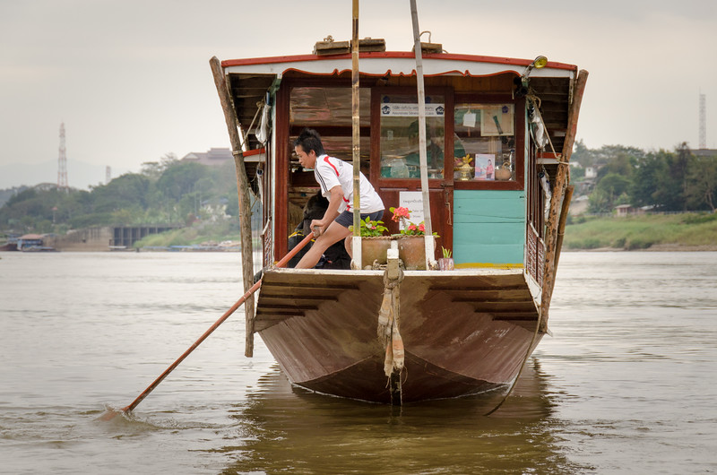 A man helping to steer a slow boat near the dock in Chiang Khong.