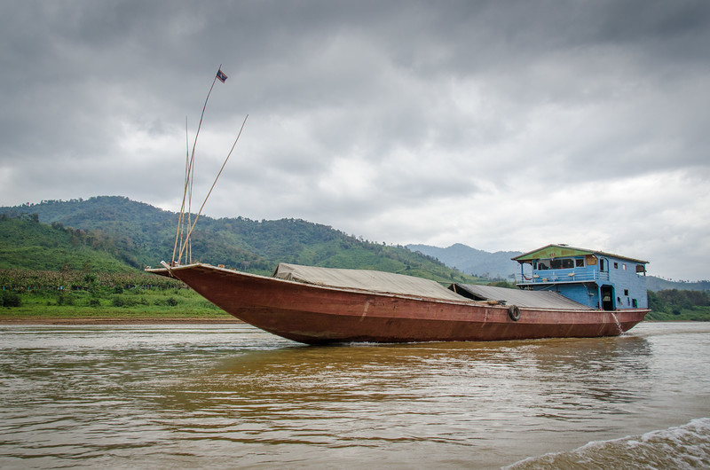A large Mekong cargo boat makes its way up the river.