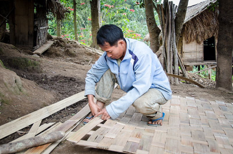 Man making a woven bamboo panel for the wall of a house.