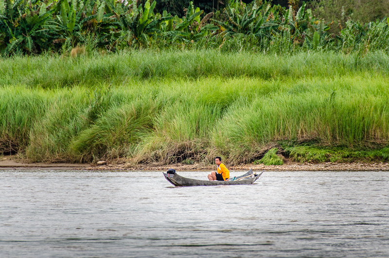 A man driving a Lao Three Plank Canoe on the Mekong.