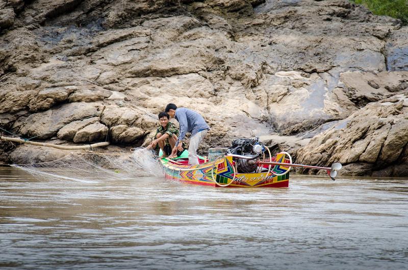 Men tending their nets from a speedboat.