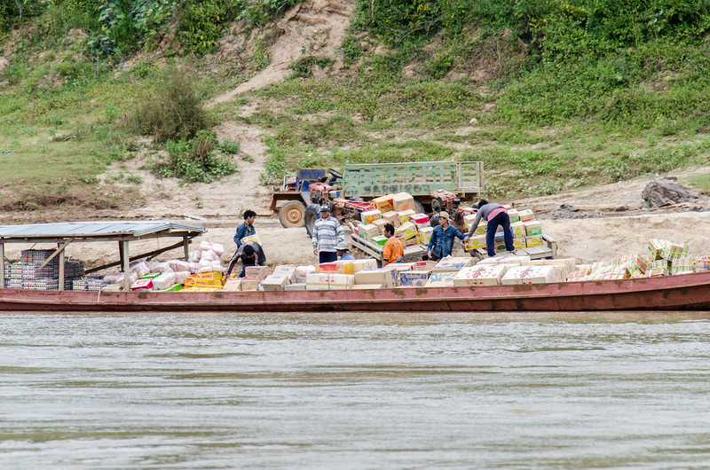 A slow boat delivering supplies to a village along the Mekong.