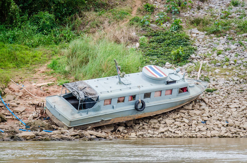 An old Thai military patrol boat beached on the Thai side of the river.