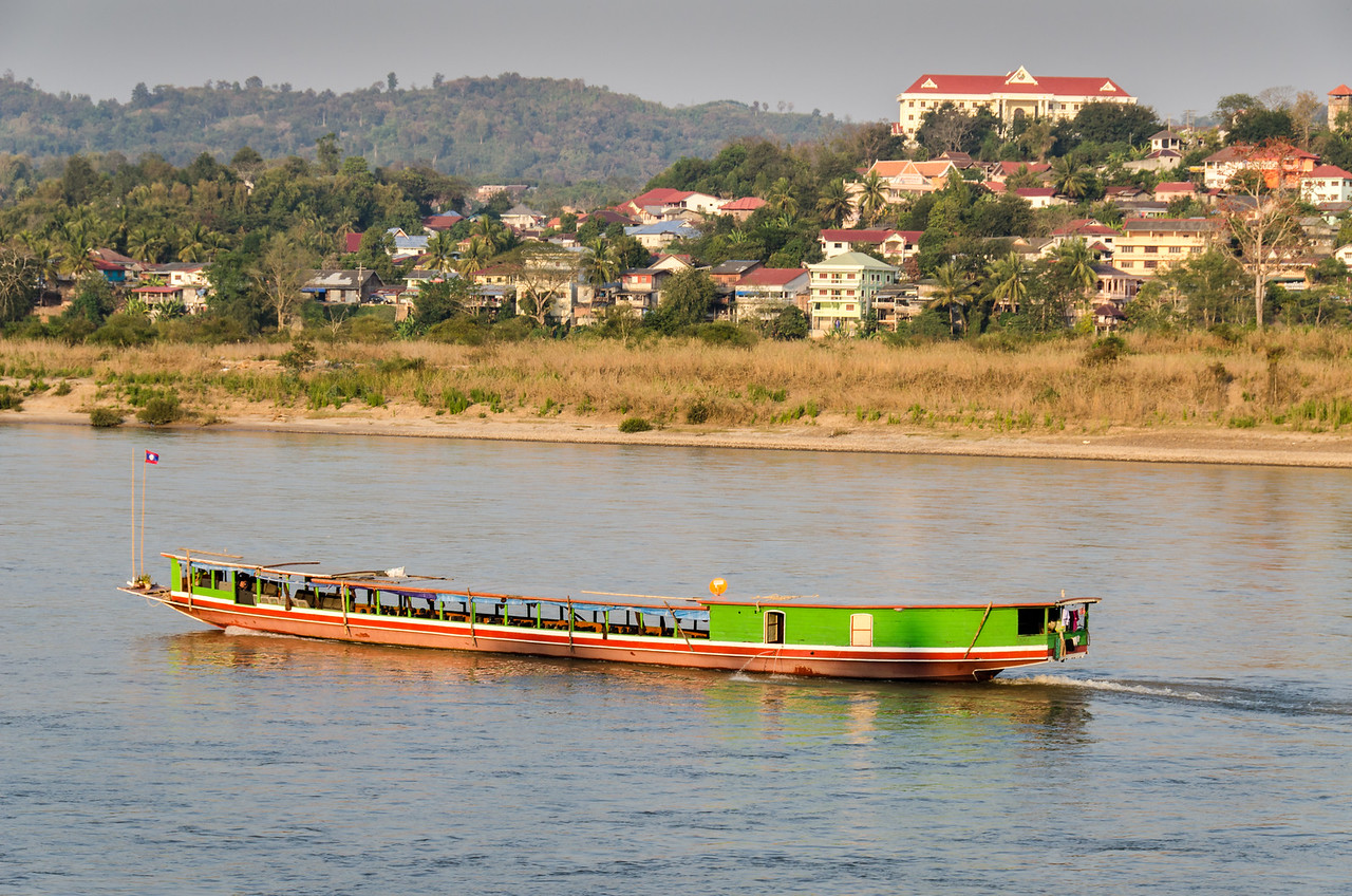 Looking across the Mekong River from Chiang Kong, Thailand to Houay Xay, Laos. A Mekong slow boat makes its way up the river late in the day.