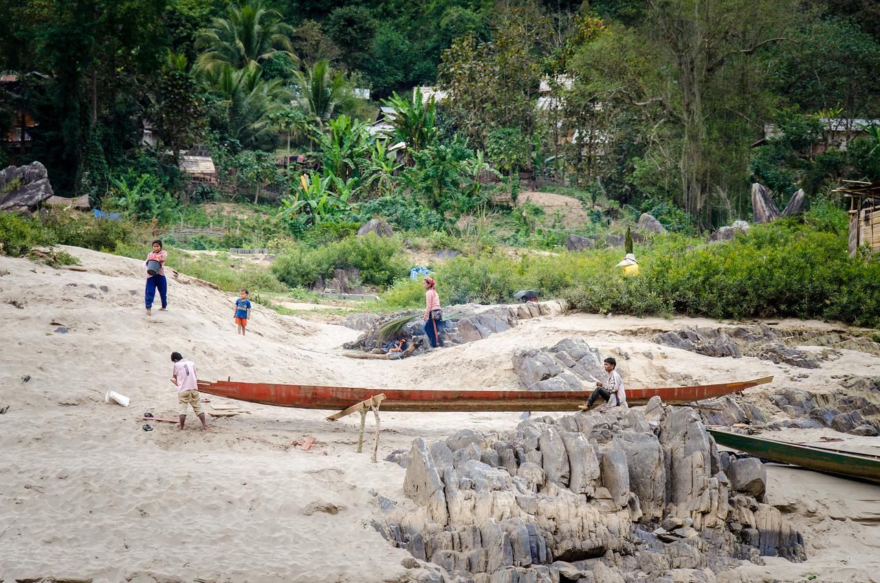 Men repairing a canoe below a village.