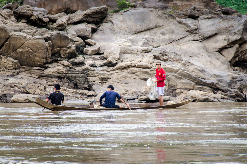 Men fishing from a traditional three-plank canoe.