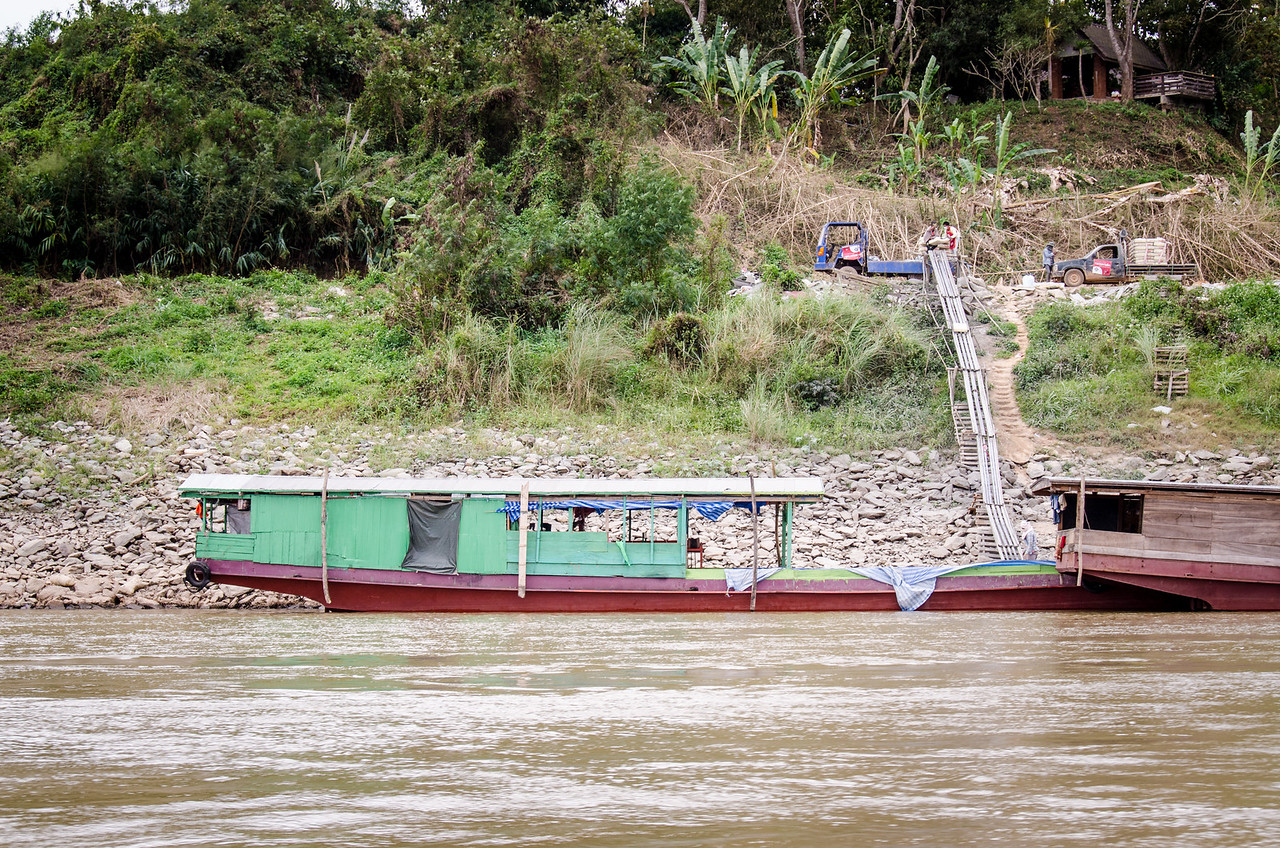 A Mekong slow boat being loaded with cargo. They slide the items down the planks to the boat.