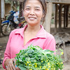 A lady carrying a bunch of morning glory. So good stir-fried!