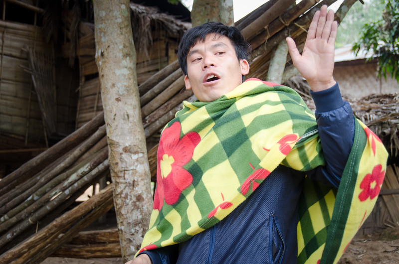 Our guide explains about the village. The government is trying to get hill tribe people to live closer to cities to improve conditions for them. By the way, that's not a traditonal Lao garment, it's a blanket off the boat. It was chilly that day.