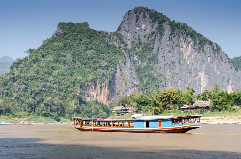 A slow boat passes Pak Ou village.