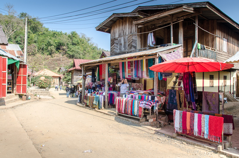 A woman selling silk goods in front of her house.