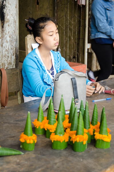 A girl sells offerings at the Pak Ou caves.