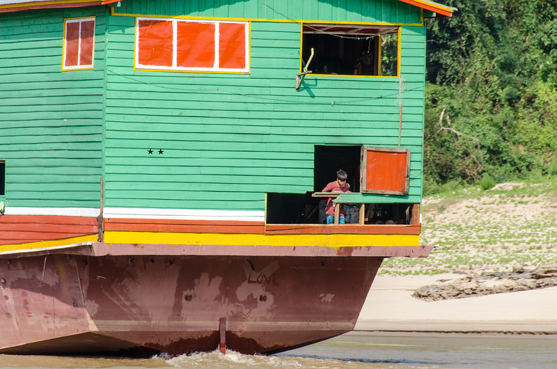 A man enjoys some fresh air from the back of a colorful slowboat.