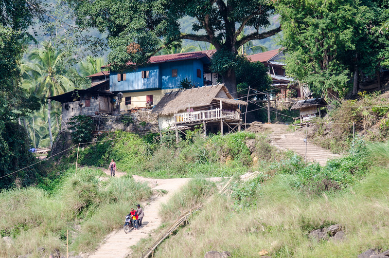 People coming down the hill to the river from a small village.