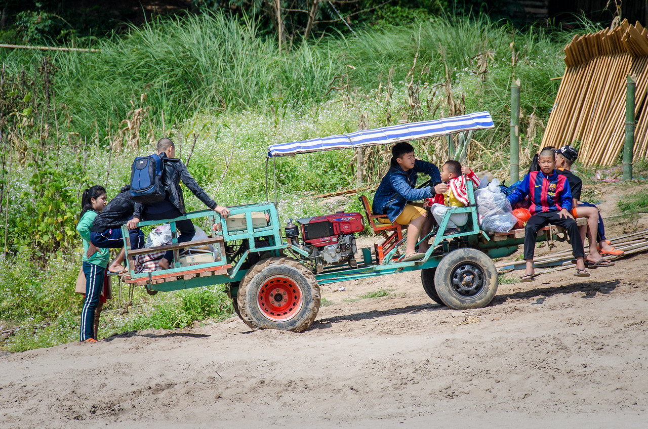 A family uses a tractor to shuttle goods and people up the hill to a small village.