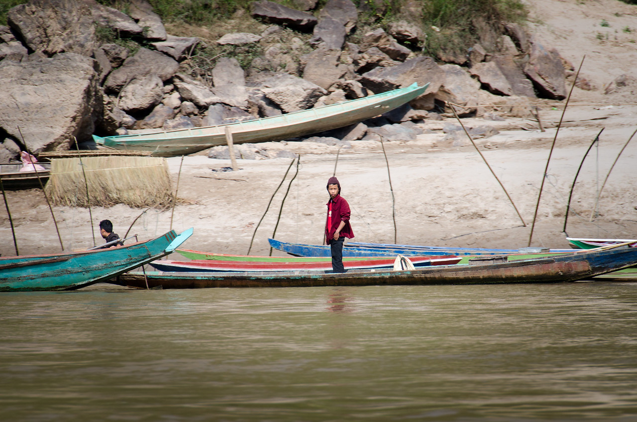 A boy standing in a canoe on the bank of the Mekong.