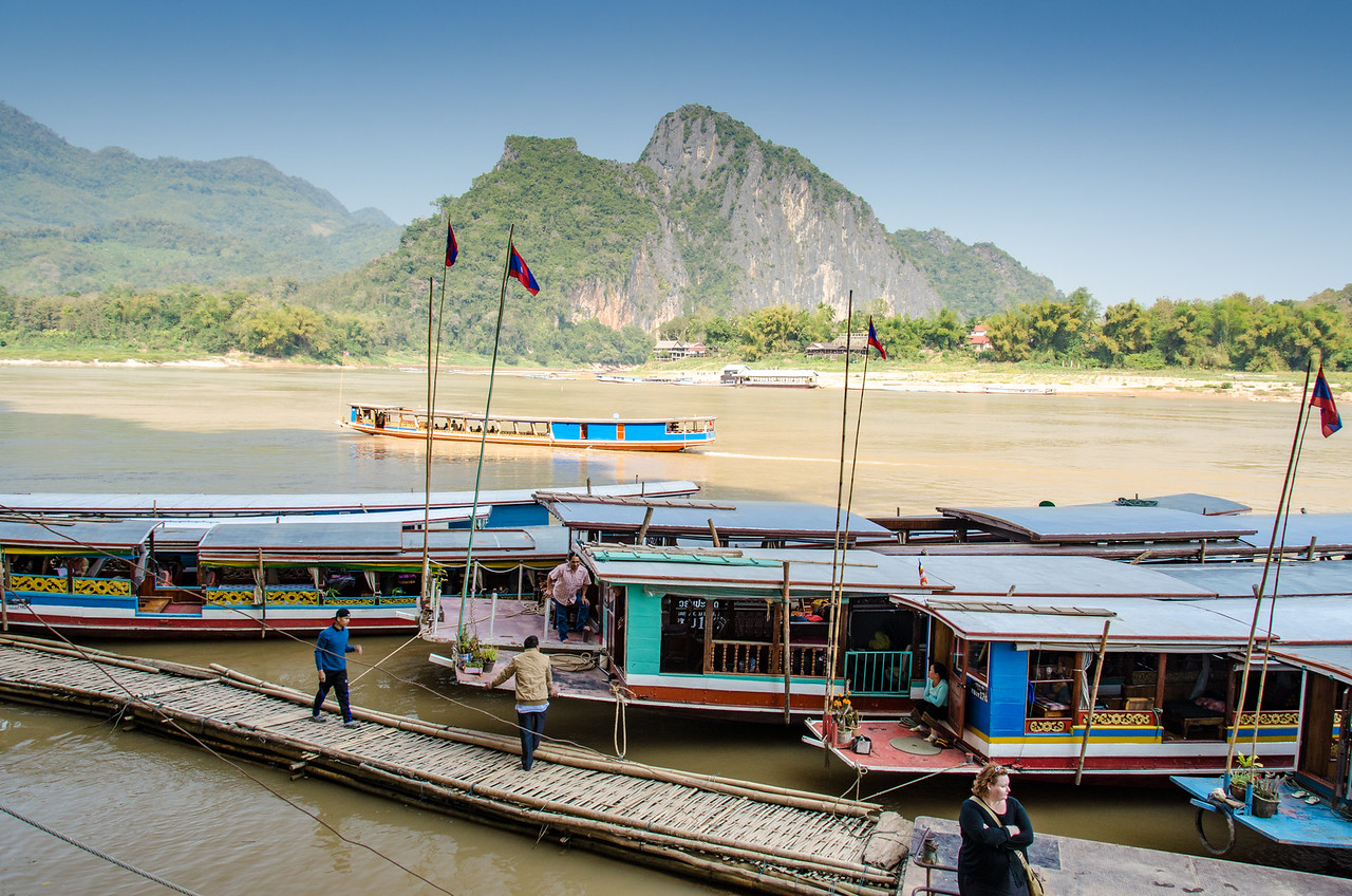 Boats docked at the Pak Ou Caves with Pak Ou Village in the background.