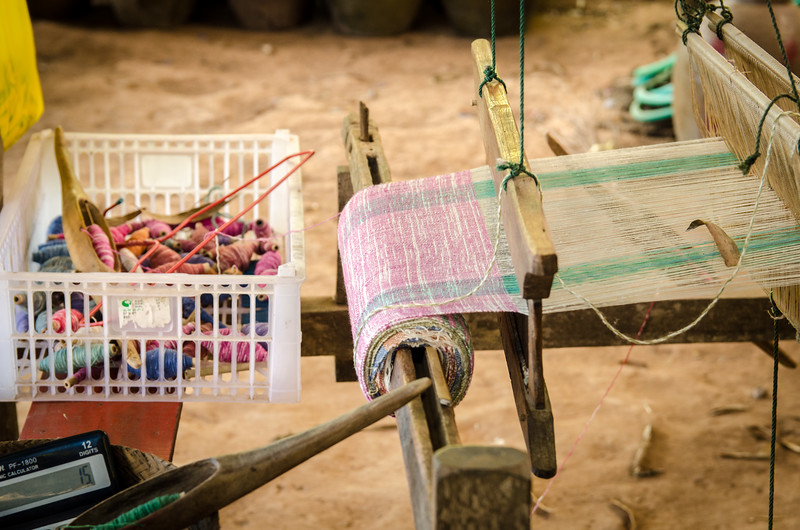 Silk being woven into a scarf on a loom.