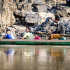A family in a motorized canoe on the Mekong. The father is holding the bamboo tiller.