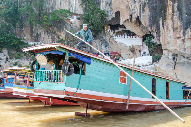 A man prepairs to fend off our boat as we dock at the Pak Ou Caves.