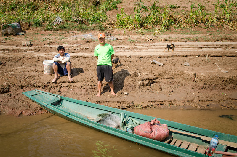 Men and puppies on the muddy bank of the Mekong.