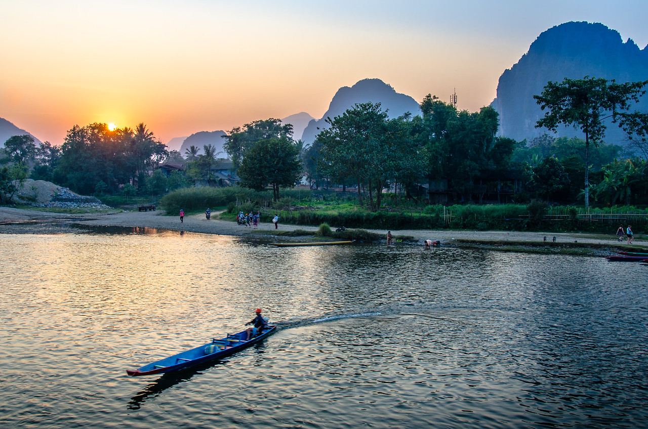The sun sets behind the karst formations on the other side of the Nam Song River.