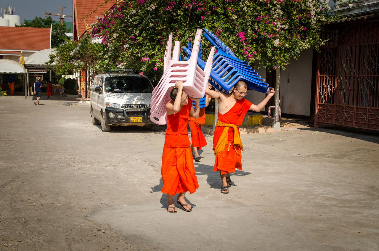 Monks carrying plastic chairs, they seemed to be setting up for something.